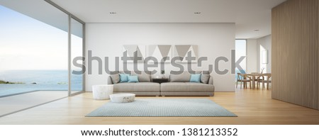 Sea view dining and living room of luxury summer beach house with swimming pool near wooden terrace. Big gray sofa in vacation home or holiday villa. Hotel interior 3d illustration.