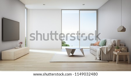 Sea view living room of luxury beach house with glass door and wooden terrace. TV on gray wall against white sofa in vacation home or holiday villa. Hotel interior 3d illustration.