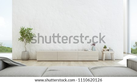 Sea view living room of luxury summer beach house with TV stand and wooden cabinet. Empty rough white concrete wall background in vacation home or holiday villa. Hotel interior 3d illustration.