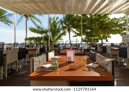 Sea view Restaurant on the tropical beach with Palm trees and blue sky. Served tables and chairs.
