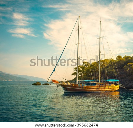 Sea voyage on classic yacht - luxury lifestyle in summer. Picturesque seashore with sailing vessel near island. Nautical landscape with wooden sailboat in retro style.