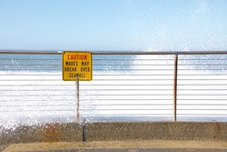 Sea Wall with caution sign about waves breaking over it. Water crashing over sign onto sidewalk. Blue sky.