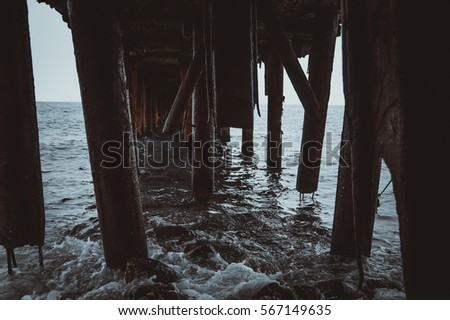 Sea washes the worn, rusted Pier #567149635