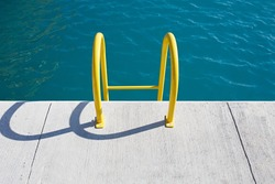 Sea water and pier with yellow stairs. Swimmingpool.