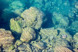 Sea water blue texture background, underwater stones