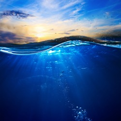 Sea water design template with underwater part and sunset skylight splitted by waterline. Water with air bubbles in sunlight