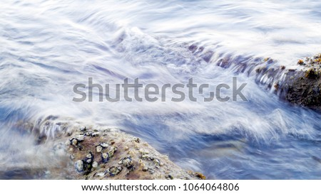 Sea water wave swash to the half-submerged rocks that covered with oyster. shot with slow shutter speed for water diffuse effect. #1064064806