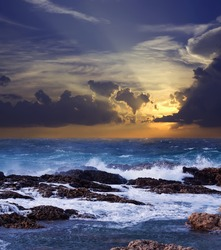 Sea wave breaking against coast  rock in sunset time