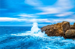 Sea wave breaks on beach rocks landscape. Sea waves crash and splash on rocks. Beach rock sea wave breaking