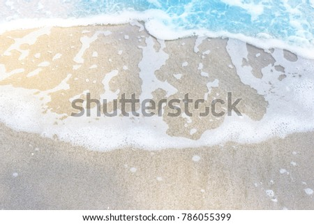 Sea wave on a sandy white beach blue sea background texture and copy space #786055399