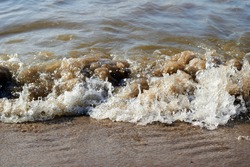 Sea wave with spray and foam near the shore. High quality photo