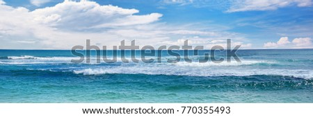 Sea waves and blue sky. Wide seascape background.