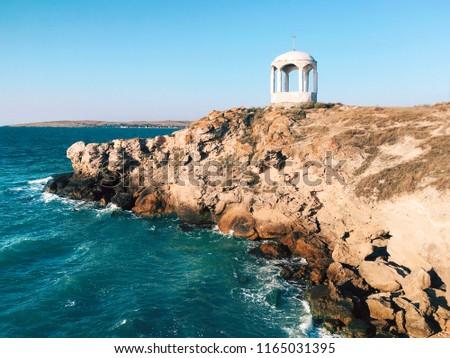 Sea waves crashing over rocks on wild stone beach. Blue sky over summer sea with sunlight reflection. Crimea, Black Sea #1165031395