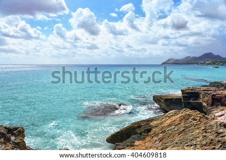 Sea waves crashing over rocks on wild stone beach in Majorca, Spain. Calm sea water, Majorca. White clouds on a blue sky over summer sea with sunlight reflection, Majorca island. Tropical sea relax #404609818
