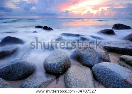 Sea waves lash line impact rock on the beach #84707527