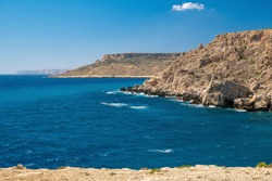 Sea with cliffs under blue sky. Summer sunny seascape. Maltese landscape.