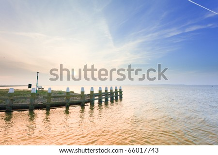 Sea with pier under blue cloudy sky, Marken, the Netherlands