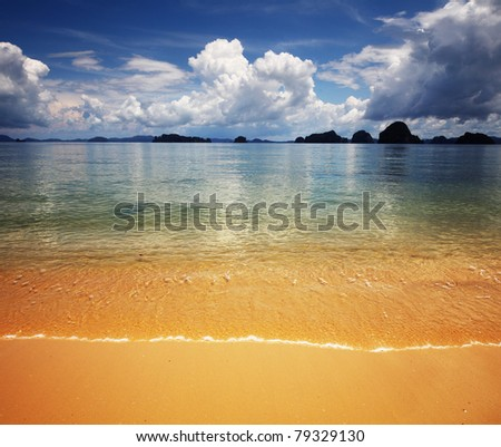Sea with waves yellow sandy coastline and deep blue sky with clouds