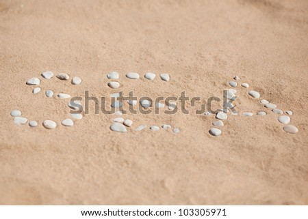 Sea word on group of stones with sand as background - stock photo