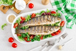 Seabass or sea bass fish roasted and fresh vegetable salad of tomatoes and lettuce, healthy food for lunch, top view