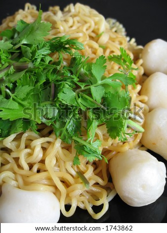 Seafood Asian stir-fry noodles with fish balls. Garnished with fresh coriander leaves.