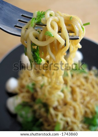 Seafood Asian stir-fry noodles with fish balls. Garnished with fresh coriander leaves. Focused at the noodles on the fork.