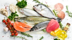 Seafood background: salmon, tuna, caviar, oysters, dorado fish and shellfish on a blue wooden background. Seafood. Flat lay.
