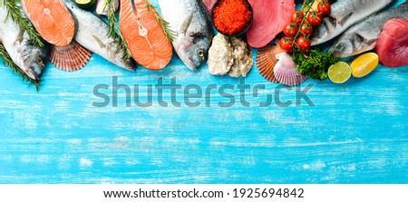 Seafood background: salmon, tuna, caviar, oysters, dorado fish and shellfish on a blue wooden background. Top view. Seafood.