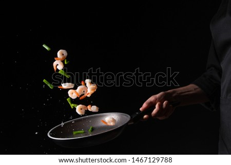 Seafood, chef cooks shrimp with brussels sprouts and pod beans in a frying pan, fry. On a black background for design, menus, restaurants, oriental cuisine, healthy food. Horizontal photo