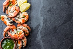 Seafood. Crabs tentacles on black plate with white wine, lemon and herbs sauce on slate background. Top view