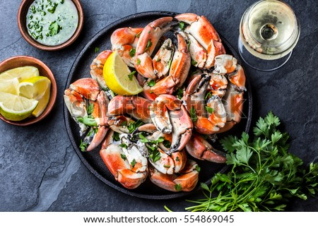 Seafood. Crabs tentacles on black plate with wite wine, lemon and herbs sauce on slate background. Top view.