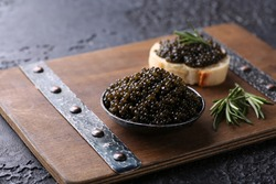 Seafood. Delicacies, snacks. Black caviar sturgeon in a dark bowl, sandwich on a dark wooden board on a black table with rosemary. Background image, copy space, horizontal