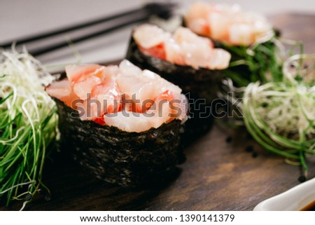 Seafood delicatessen gunkan maki sushi rolls on wooden plate. Food blog and culinary, restaurant menu