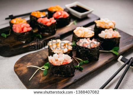 Seafood delicatessen gunkan maki sushi rolls on wooden plates. Different gourmet snacks. Luxury lifestyle, expensive food, restaurant menu