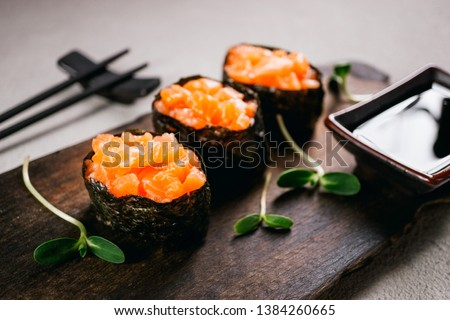 Seafood delicatessen salmon gunkan maki sushi rolls on wooden plate. Delicacy gourmet snacks. Luxury lifestyle, expensive food, restaurant menu