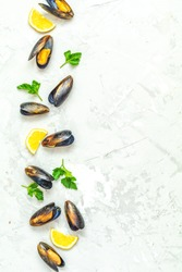 Seafood mussels with lemon and parsley on light gray concrete table surface, top view, copy space for you text. Food background
