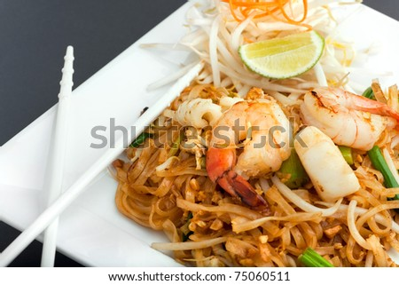 Seafood pad Thai dish of fried rice noodles on a square white plate with chopsticks and grated carrot garnish.