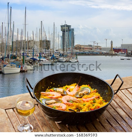 Seafood paella with glass of wine in seaside cafe port of Barcelona