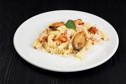 Seafood Pasta with mussels salmon and shrimps with basil in white plate on black wooden background.