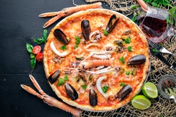 Seafood Pizza. Shrimp, mussels, seafood. On a wooden background. Top view. Free space for your text.