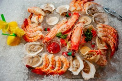 Seafood platter or seafood tower. Fresh sea food: lobster, jumbo shrimp, crab claws, crab legs, oysters, clams served with cocktail sauce, lemons and mignonette sauce. Classic fine dining appetizer.