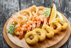 Seafood platter with deep fried squid rings, shrimp and onion rings decorated with lemon on cutting board on wooden background. Mediterranean appetizers. Top view