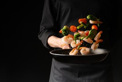 Seafood, Professional cook prepares shrimps with vegetables. Frost in the air, Cooking seafood, healthy vegetarian food and food on a dark background. Horizontal view. Eastern kitchen, banner