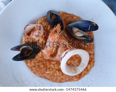 Seafood Risotto Served On a White Plate, Variety of Cooked Seafood: Squids, Shrimps, Mussels, Octopus with Rice, Tomato Sauce and Parmesan Cheese, Delicate and Creamy Seafood Dish #1474375466