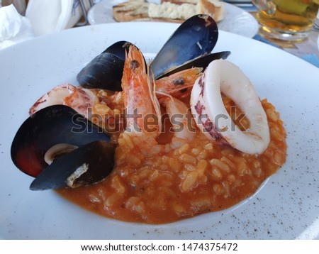 Seafood Risotto Served On a White Plate, Variety of Cooked Seafood: Squids, Shrimps, Mussels, Octopus with Rice, Tomato Sauce and Parmesan Cheese, Delicate and Creamy Seafood Dish #1474375472