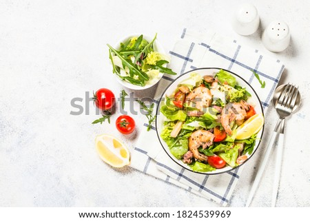 Seafood salad with fresh leaves tomatoes and fried seafood. Top view at white table. Foto d'archivio ©