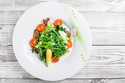 Seafood salad with mussels, squids, octopus, arugula, lettuce and cherry tomatoes on wooden background. Mediterranean food. Top view
