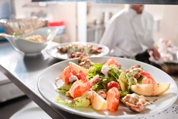 Seafood salad with stuffed mussel and prawns on commercial kitchen