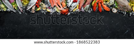 Seafood. Set of fish, crustaceans, oysters, mussels and seafood on a black stone background. Free space for your text. Photo stock ©