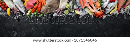 Seafood. Set of fish, crustaceans, oysters, mussels and seafood on a black stone background. Free space for your text.